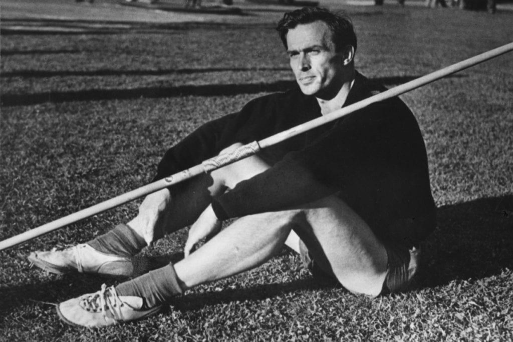 Hall of Fame Tapio Rautavaara istuu nurmikolla keihään kanssa Urheilumuseo